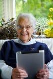 Lycklig gammalare kvinna som använder en tablet som ser kameran och skratta Royaltyfria Bilder