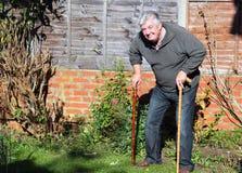 Lycklig gammalare man med två gå sticks. Arkivbild