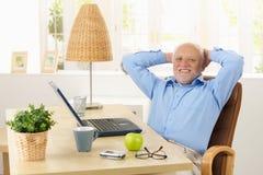 Lycklig gammalare man som ler på skrivbordet Royaltyfria Bilder