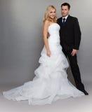 Lycklig gift parbrudbrudgum på grå bakgrund royaltyfri bild
