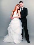 Lycklig gift parbrudbrudgum på grå bakgrund royaltyfria foton