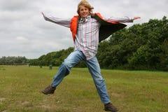 lycklig glädjebanhoppning för pojke Arkivfoton