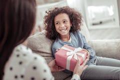 Lycklig glad flicka som mottar en stor gåva från moder royaltyfri bild