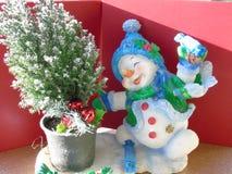 Lycklig glad julsnögubbe som åker skridskor runt om ett Xmas-träd arkivfoton