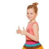 Lycklig glad liten flicka som ler upp visningtummar, isolerat på vit bakgrund arkivbilder