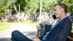 Lycklig gladlynt affärsman i en dräkt som talar på telefonen som ler sammanträde på bänken i en parkera på solig sommardag arkivfilmer