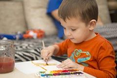 Lycklig gladlynt barnteckning med borsten genom att använda hjälpmedel för en målning lego för hand för byggnadsbegreppskreativit royaltyfria bilder