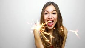 Lycklig gladlynt flicka som rymmer bengal ljus på partiet Stående av den unga kvinnan som firar med tomtebloss som isoleras på vi arkivbilder