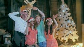Lycklig gladlynt grupp av vänner på julpartiet Hälsning in i kamera och att ha gyckel som ler fira helgdagsafton för ` s för nytt stock video
