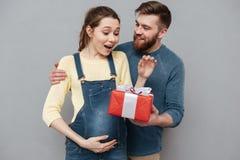 Lycklig gladlynt make som ger den närvarande asken till hans gravida fru arkivfoto