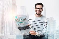 Lycklig gladlynt man som visar skärmen av hans bärbar dator arkivfoto