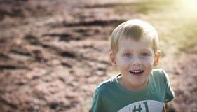 Lycklig gladlynt pojke som utomhus går Arkivbilder