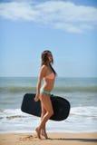 Lycklig gladlynt spring för glad surfareflicka som surfar på havstrandvatten Kvinnlig bikini som går mot vågor med surfingbrädan Arkivfoto
