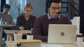 Lycklig gladlynt ung arbetare av appellmitten i huvud-telefoner som ler och arbetar på bärbara datorn arkivbild