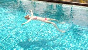 Lycklig gladlynt ung kvinna i det röda simningföljet som ligger på vatten i simbassäng Härlig solig dag arkivfilmer