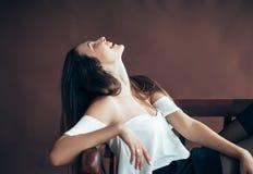 Lycklig gladlynt ung kvinna som kopplar av på bänk fotografering för bildbyråer