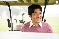 Lycklig golfare som kör hans golfbarnvagn Royaltyfri Foto