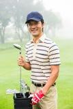 Lycklig golfare som tar klubban från golfpåse Fotografering för Bildbyråer