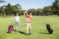 Lycklig golfare som tar skottet Arkivbild