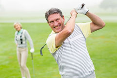 Lycklig golfare som teeing av med partnern bak honom Royaltyfri Foto