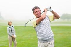 Lycklig golfare som teeing av med partnern bak honom Arkivbild