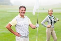 Lycklig golfareinnehavflagga för att hurra partnern Royaltyfria Foton