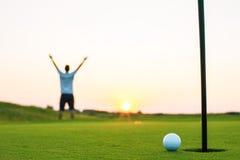 Lycklig golfspelare på en golfdomstol på solnedgången Arkivfoton