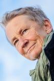 Lycklig grå färg-haired äldre utomhus- kvinnapensionär arkivfoto