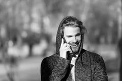 Lycklig grabb i huvsamtal på mobiltelefonen på soligt utomhus- Skäggigt manleende i huv på ny luft Macho le för mode Arkivbild