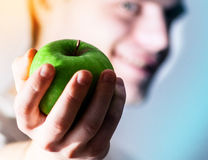 Lycklig grabb med ett grönt äpple i hand, begreppet av ett sunt l fotografering för bildbyråer