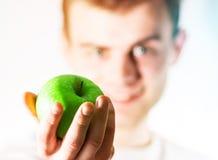 Lycklig grabb med ett grönt äpple i hand, begreppet av ett sunt l arkivbilder