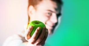 Lycklig grabb med ett grönt äpple i hand, begreppet av ett sunt l arkivbild