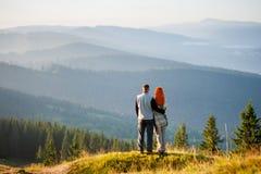 Lycklig grabb och flicka i bergen i morgonen arkivfoton