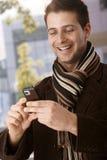 Lycklig grabb som ser den mobila telefonen Arkivfoto