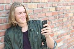 Lycklig grabb som utanför använder en smart telefon med utrymme för kopia eller text arkivbilder