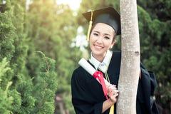 Lycklig graderad studentflicka, lyckönskan - doktorand- utbildningsframgång Arkivfoton