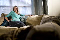 lycklig gravid avslappnande sofakvinna royaltyfri bild