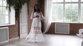 Lycklig gravid dam i den vita klänningdansen som omkring virvlar i ljust rum Härligt brunett i förväntan brigham stock video