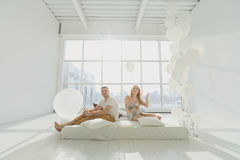 Lycklig gravid familj med en liten son som spelar mot fönstret i ett vitt rum Royaltyfria Foton