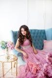 Lycklig gravid kvinna i rosa färgklänningsammanträde i en blå stol skjutit mode Arkivfoton