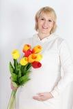 Lycklig gravid kvinna i vit med buketten av tulpan Royaltyfri Bild