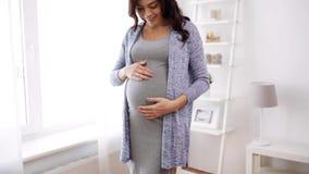 Lycklig gravid kvinna med den hemmastadda stora magen lager videofilmer