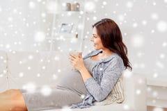Lycklig gravid kvinna med koppen som hemma dricker te Fotografering för Bildbyråer