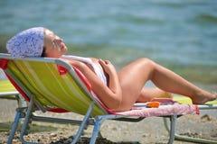 Lycklig gravid kvinna på stranden på soluppgång Royaltyfri Foto