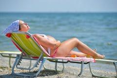 Lycklig gravid kvinna på stranden på soluppgång Fotografering för Bildbyråer