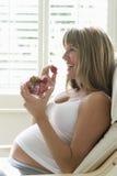 Lycklig gravid kvinna som äter jordgubbar Royaltyfri Fotografi