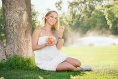 Lycklig gravid kvinna som äter nya persikor Royaltyfri Bild
