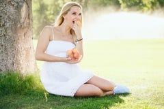 Lycklig gravid kvinna som äter nya persikor Royaltyfri Fotografi