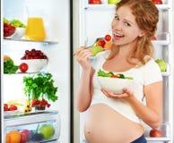 Lycklig gravid kvinna som äter sallad nära kylskåpet Fotografering för Bildbyråer
