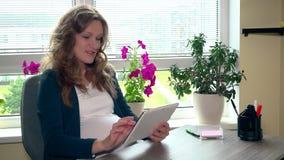 Lycklig gravid kvinna som använder minnestavladatoren på arbete arkivfilmer